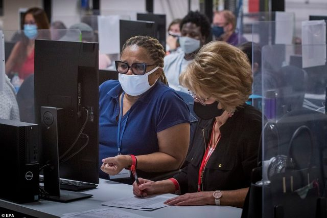 Adjudicators continue to check ballots at the Maricopa County Recorder's Office Thursday as votes continue to be counted in several key battleground states
