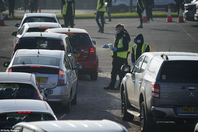 Cars queue outside a coronavirus testing centre at Wavertree Sports Park in Liverpool yesterday morning
