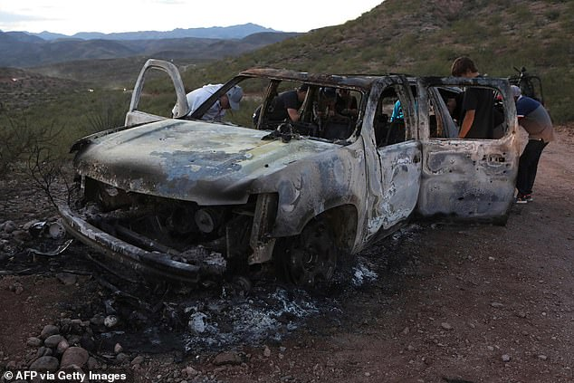 Members of the LeBarón family search through the burned car where five of the nine Mormon mothers and children were killed and burned during an ambush launched by a cartel gang in Bavispe, Sonora, on November 4, 2019