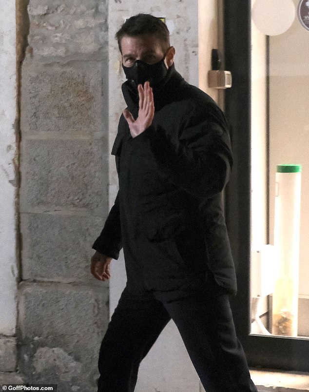 Wrapped up warm:Tom wrapped up in a cosy black padded jacket and a matching mask as he headed out for an evening walk