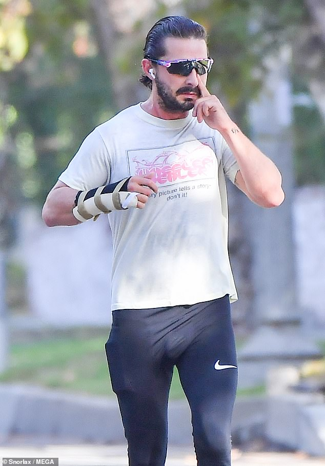 Stepping out: The actor wiped a smudge off one of his frames during his run