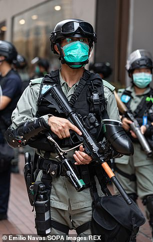 An armed police officer on guard in Hong Kong is pictured in May, 2020