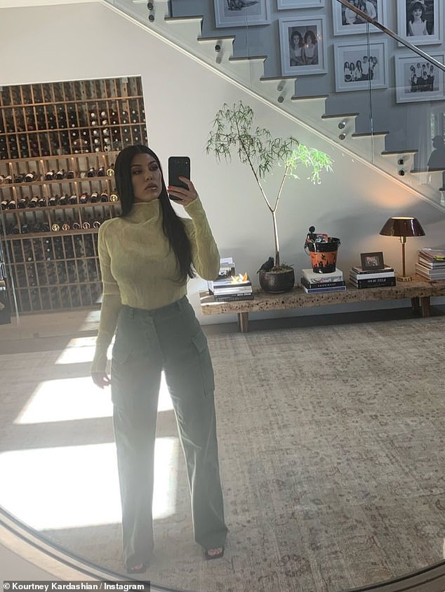 Elegant:She was unmissable in a sheer ribbed pale yellow blouse, which she had tucked into olive cargo pants