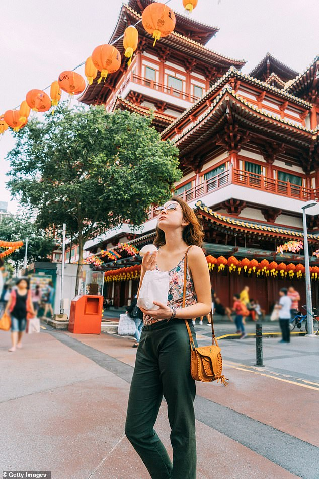 Trade and Tourism Minister Simon Birmingham confirmed he is in talks with Singapore's trade officials over a possible travel bubble (pictured: a tourist eats a Chinese bun in Chinatown in Singapore)