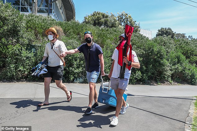La Trobe University Epidemiologist Hassan Vally said new cases need to be contained (pictured, men carry a cooler to a park in Melbourne as restrictions eased on November 3)
