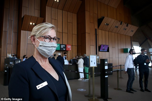 Coronavirus could be eliminated in Australia if Victoria and New South Wales continue to have low case numbers (pictured, greeter wearing as mask at the Sydney Opera House on Nov 1)