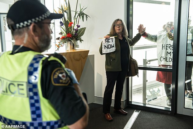 One woman (pictured) even glued her hand to a glass window during the climate change protest