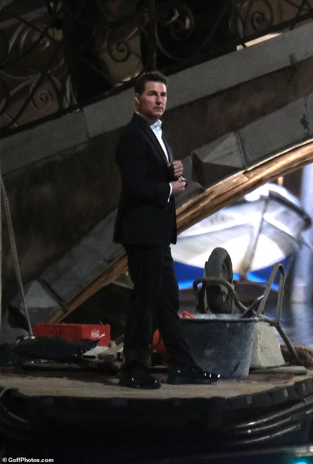 Ready for action: Meanwhile, Tom, who looked dapper in a black suit, also joined his co-star in filming the dangerous scenes on the water