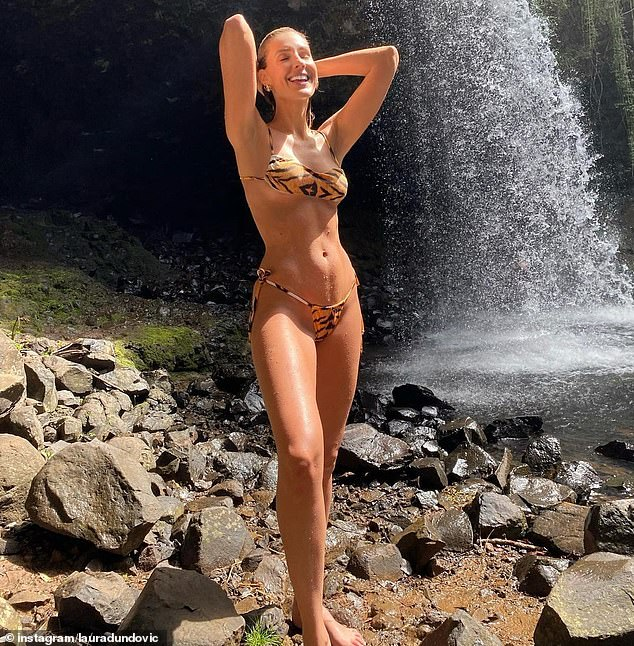Jungle girl! Laura appeared drenched, and was seen wringing her hair out with her hands, as she posed in front of a waterfall