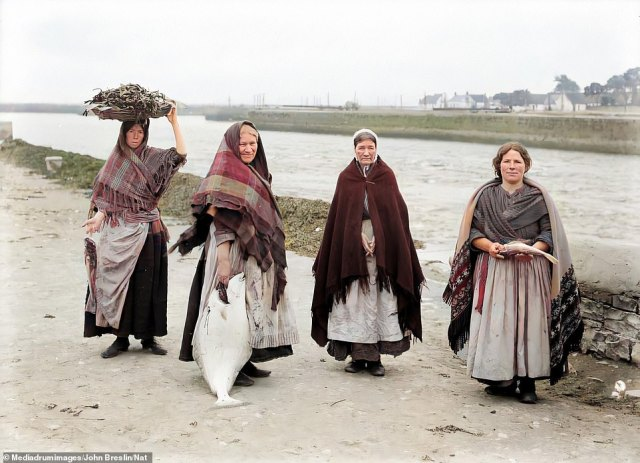 A group of women from Claddagh - Nonnie O'Donnell, Mary Rodgers, Kitty Connelly and a Mrs Gill - pose for a picture by the waterside during a fishing trip in around 1905. The area, formerly known as The Claddagh, was once a fishing village walled off from the nearby city of Galway, and is thought to be one of the oldest fishing towns in Ireland - as evidenced by the catch which the women in this picture are displaying - but the village was brought low by a tuberculosis outbreak in 1927