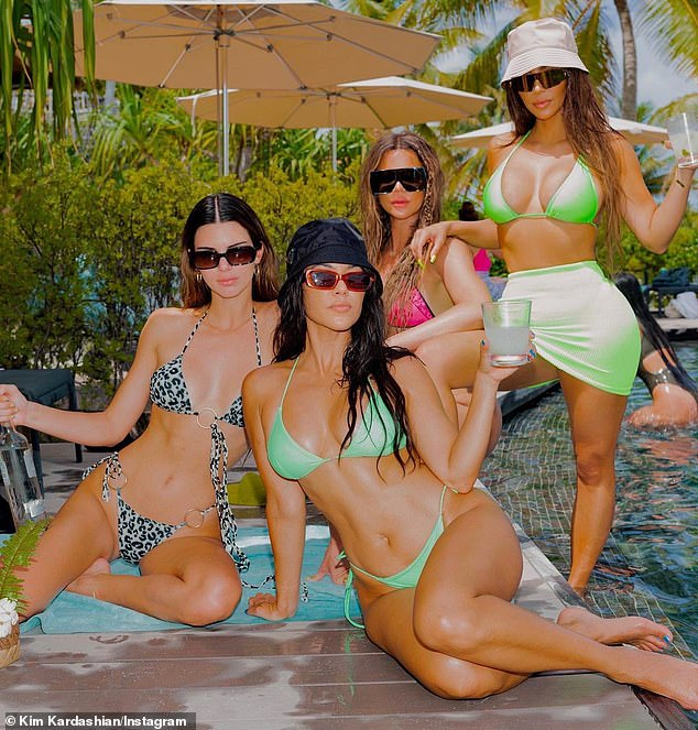 Seeing Green: Kim showed off her flat stomach and sculpted figure in a neon green bikini while going for a swim.  She also showed off the costume while posing with her sisters