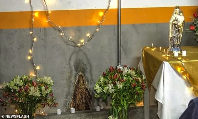 Flowers, candles and fairy lights adorn the space, alongside a statue of the Virgin sitting on a makeshift altar. Some have said the image is simply the result of water damage, while others in the devoutly Catholic country consider it to be a 'miracle'