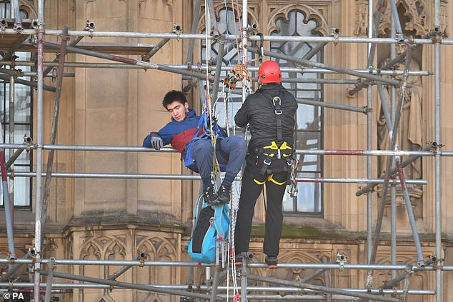 A protester from Action for Climate Truth and Reparations is removed after climbing the scaffolding outside the Houses of Parliament
