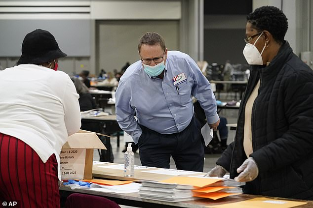 Randy Osborne, Republican party observer, looks as officials sort ballots in Georgia Saturday