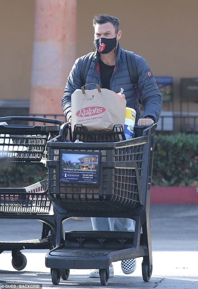 Carting along: Brian wore a poofy blue winter jacket with a simple black top on underneath, and paired it with acid wash jeans and checked Vans shoes