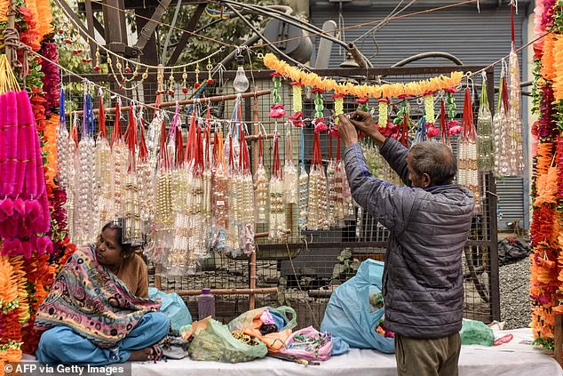 More than one billion people in India celebrated Diwali, the Hindu festival of lights, yesterday despite an upturn in infections. Pictured: Vendors selling garlands in Amritsar, India