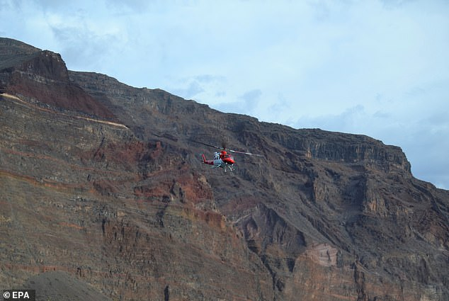A Spanish emergency helicopter searches for possible victims after the massive landslide in the beach area on Sunday
