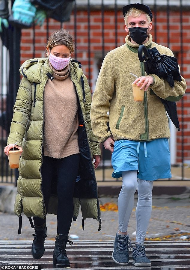 Coffee run: The 33-year-old kept warm in a tan turtleneck and a puffy green jacket, as they grabbed some iced coffee drinks, after dropping of Banks, two