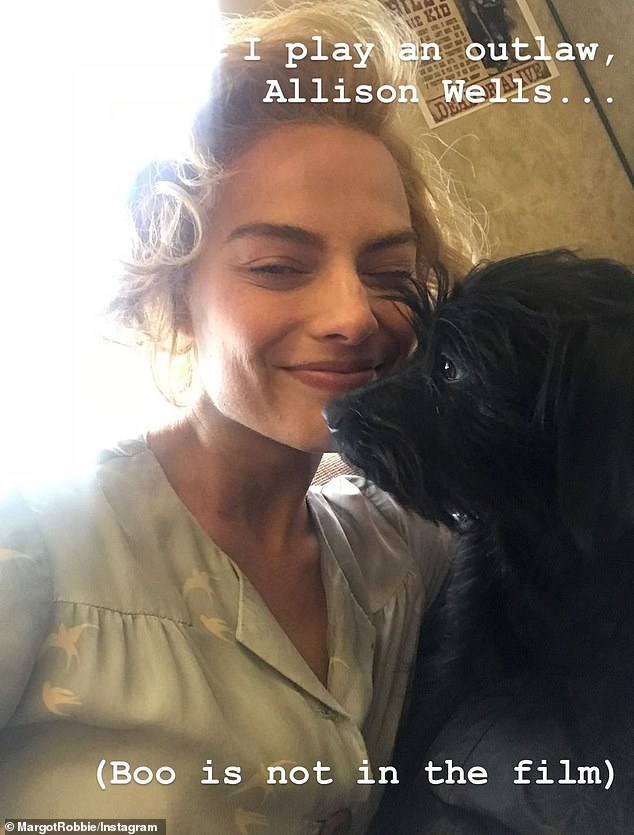 Sweet: One picture showed Margot with rollers in her hair as she prepared for a scene, and cuddled a dog