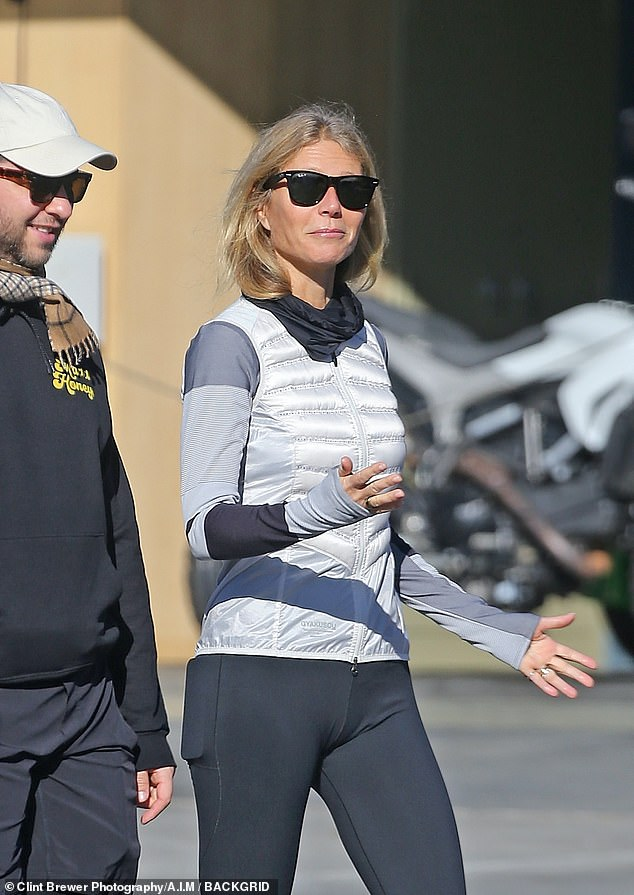 Chit chat:Gwyneth chatted animatedly to one of their friends as she strolled along in a sporty white sports top with dark and light grey striped arms