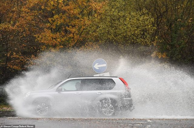 Another of England's major motorways - the M27 near Southampton - was closed yesterday due to the deluge and had to be sealed off by police near the M271 junction. Pictured: Cars driving through floodwater in Cadnam