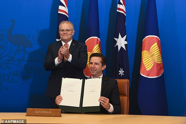 Prime Minister Scott Morrison (left) and Trade Minister Simon Birmingham (front) after signing the Regional Comprehensive Economic Partnership on Sunday during a virtual ceremony
