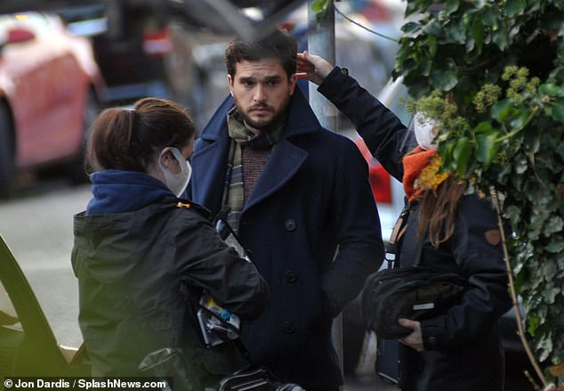 Practicalities: Kit, who wrapped up warm in a thick navy overcoat and tartan scarf, was also spotted having his make-up touched up by an assistant wearing a mask