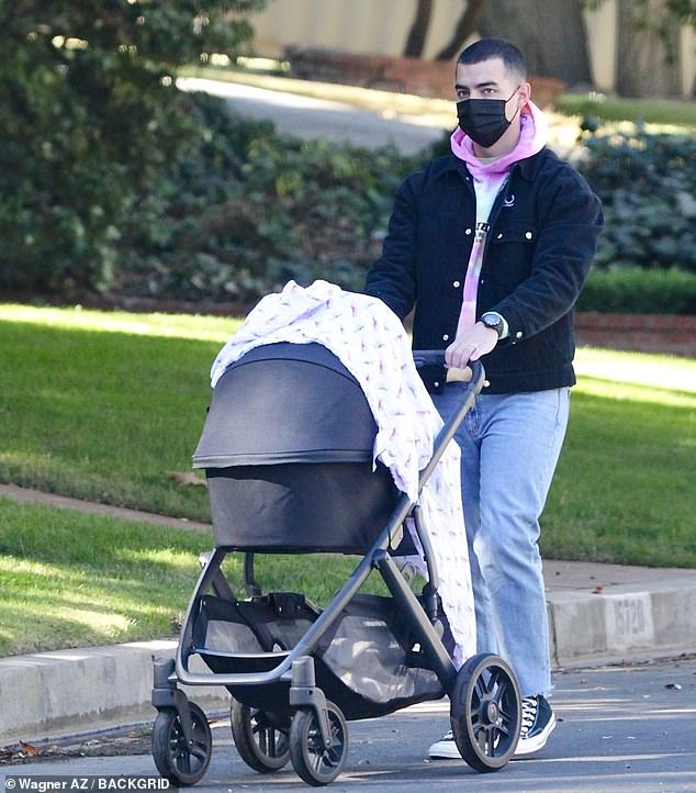 Joe Jonas is the image of a doting dad as he takes his baby daughter Willa for a stroll