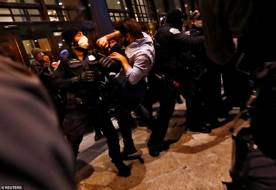 A man is thrown into the air by Washington Metropolitan police officers as Trump supporters and anti-fascist protesters clash at the front door of the Capital Hilton hotelin downtown Washington D.C. on Saturday night
