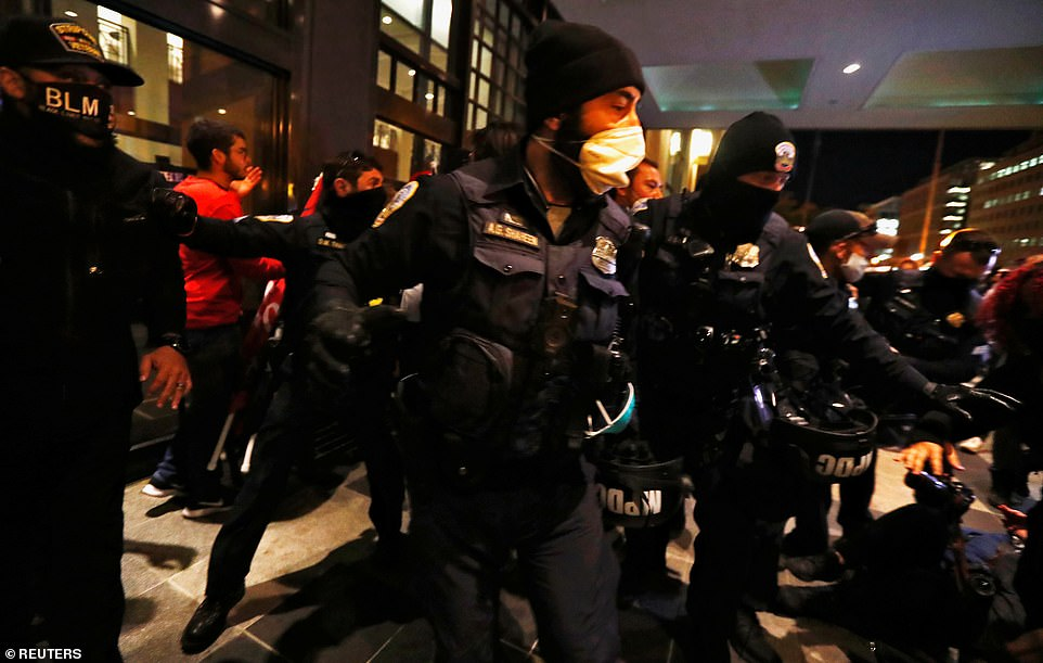 D.C. police officers react as Trump supporters and anti-fascist protesters clash at the front door of the Capital Hilton hotel