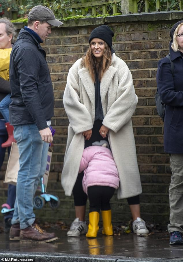 Smile: Binky laughed as little India larked about in an attempt to stay dry from the rain