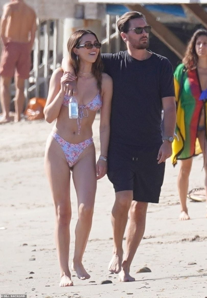 Smiley:As she made her way down the crowded beach in Scott's arm, Amelia could not help but flash a few smiles