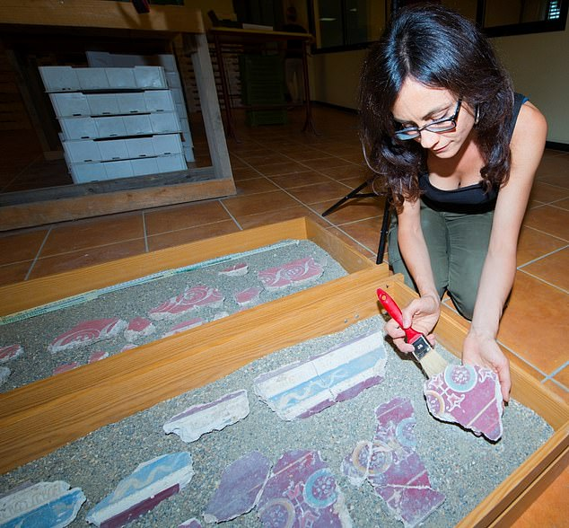 Archaeologist Silvia Fortunati brushes fragments of the interiors of the historical palace, which reveal 'lively' frescoes - wall paintings applied to wet plaster