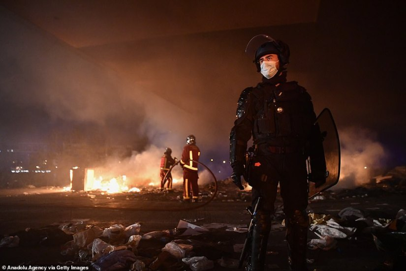 An officer in heavy riot gear and a face mask stands guard as firemen douse the inferno at the migrant camp last night