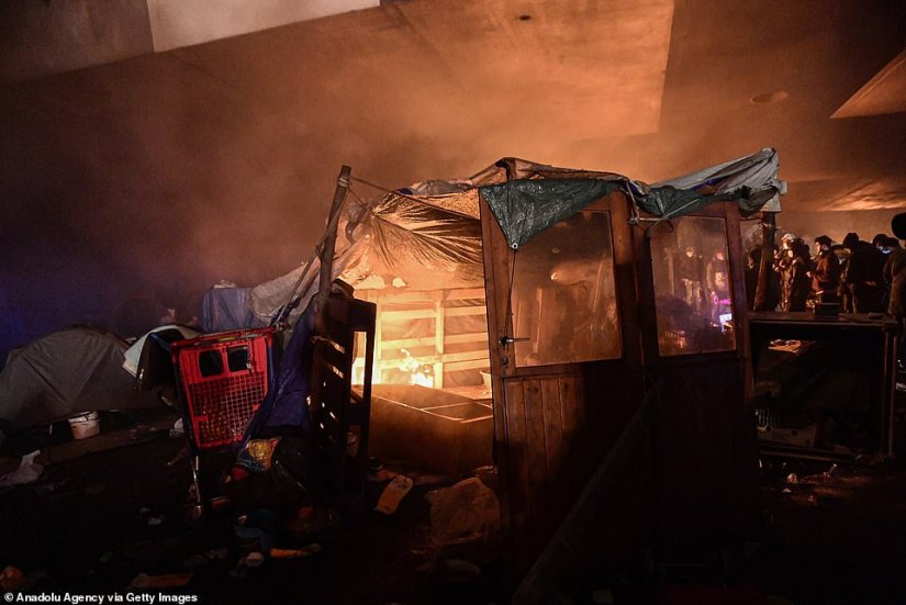 A makeshift shelter constructed of wooden pallets, a door and tarpaulin sheets goes up in flames