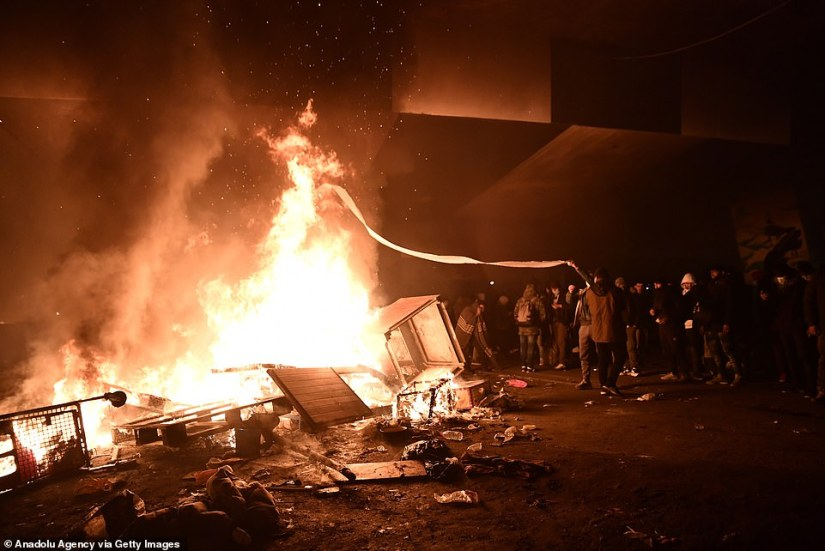 Fuel is hurled onto the bonfire as migrants put up a resistance to be being carted off to more secure facilities in the Ile-de-France region