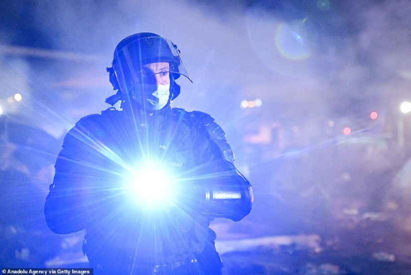 A riot policeman shines a torch at the camp