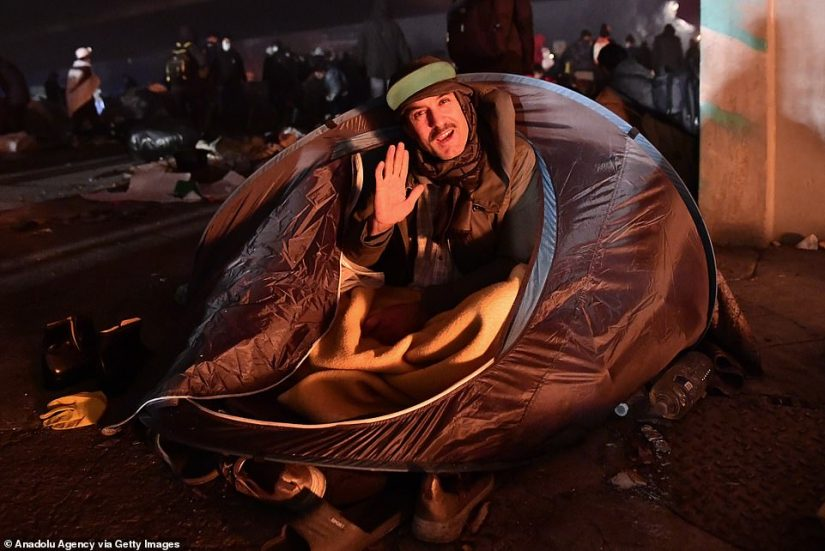 A migrant waves from his tent as chaos unfolds behind him