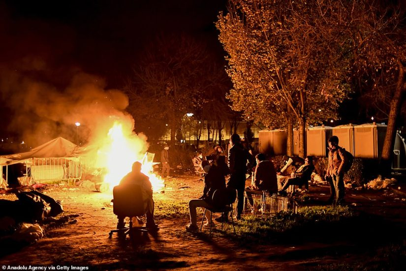 A group of migrants sit around a bonfire ahead of their removal from the camp