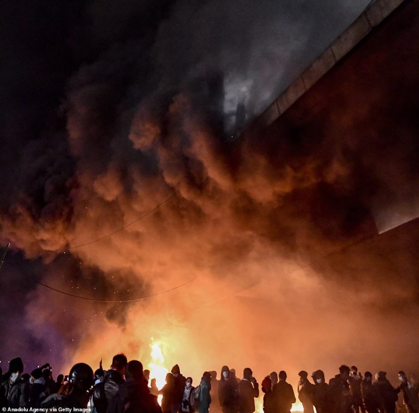 A tremendous column of thick black smoke rises from the fire constructed by the migrants last night in furious scenes in the Paris suburbs