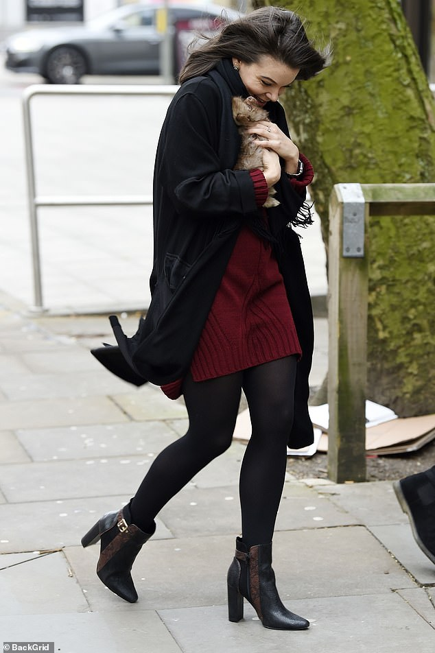 Besotted: The actress added height to her frame with black boots and she styled her raven tresses in a straight style as she cradled her fluffy bundle of joy