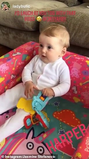 Sweet: Harper looked cute as a button in a light pink onesie while sitting in a Peppa Pig chair and clutching a colourful children's toy