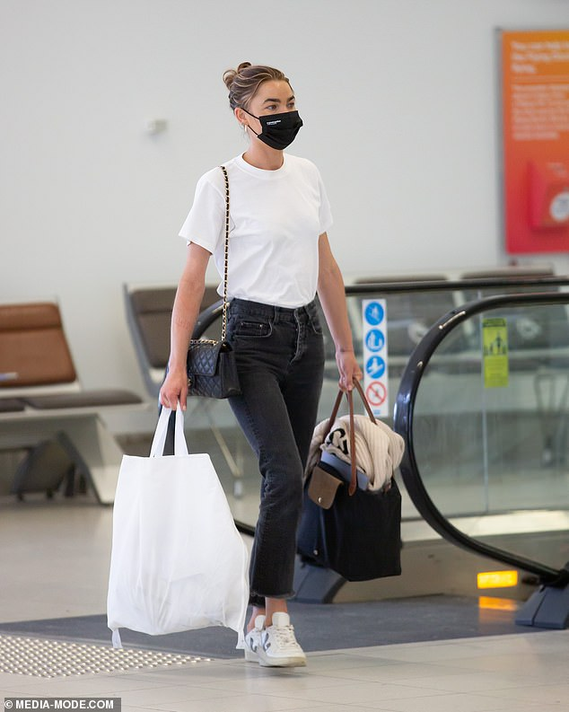 Safety first: Bambi Northwood-Blyth wore a face mask as she strolled through the airport carrying a designer bag and waited for her luggage