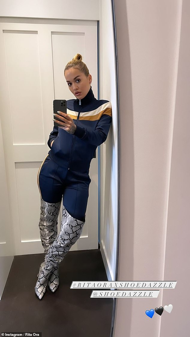 Versatile: The Masked Singer judge also modelled a navy tracksuit, which she dressed up with her new animal print thigh-high bootsfrom her Shoe Dazzle collection