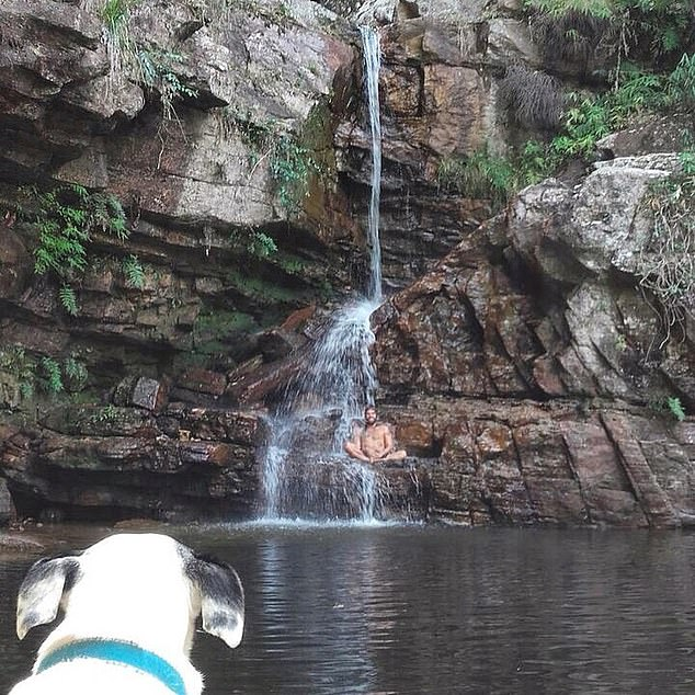 Mr. Pereira sitting under a waterfall watched by his dog