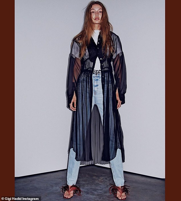 City girl:The model worked a sheer, midnight blue duster that cascaded over her classic acid wash jeans and plain white T-shirt