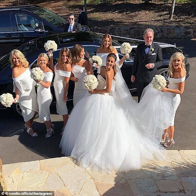 Angelic! The bridesmaids cut demure figures in their unique calf-length frocks, pairing their custom-made couture frocks with strappy white heels and white floral bouquets