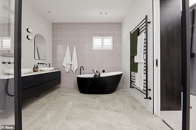 Luxurious: Their master en suite also has a splash of colour, with white and pink tiled walls, concrete-looking floors, a striking black and white bathtub, a double shower and black hardwear
