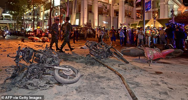 Devastating: The huge blast killed 20 people and left 125 others with horrific injuries and traumatising memories. Pictured: Thai soldiers inspect the scene after a terror bombing rocked the religious shrine in central Bangkok