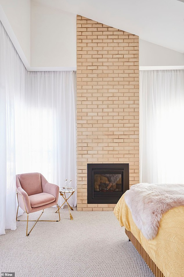 What a room: The master bedroom features a fireplace with exposed bricks, stunning pink and grey featured wall paper and a unique wooden bed, with pink furnishings
